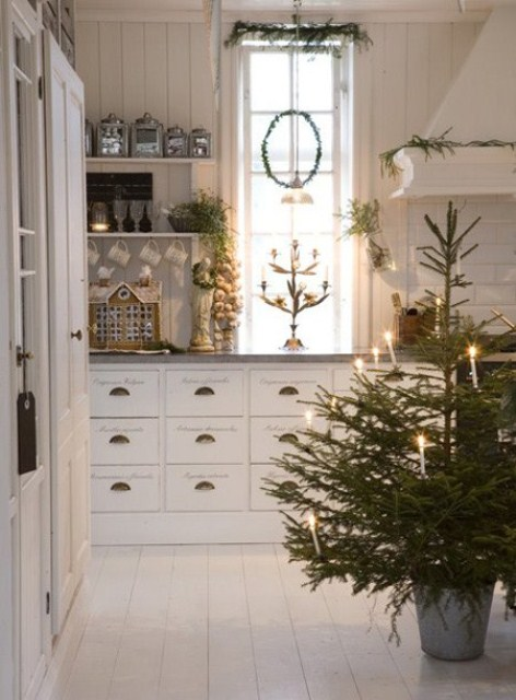 a non-decorated Christmas tree with candles in a bucket, evergreens all around the space for a cozy and natural feel
