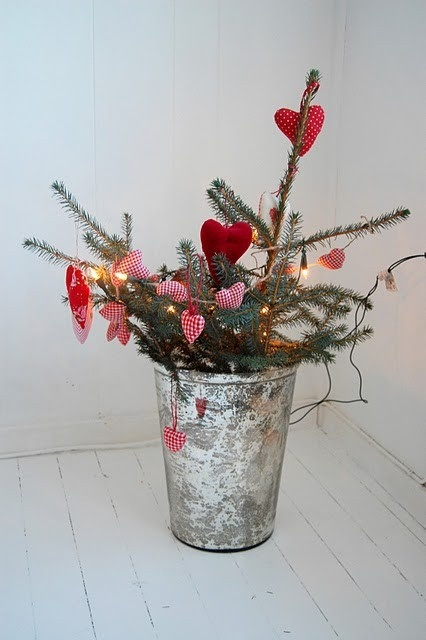 evergreen branches with red hearts and lights in a galvanized bucket for a Scandinavian Christmas feel