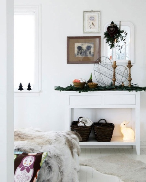 evergreens, baskets, candles in wooden candleholders, a bowl with metallic ornaments and greenery