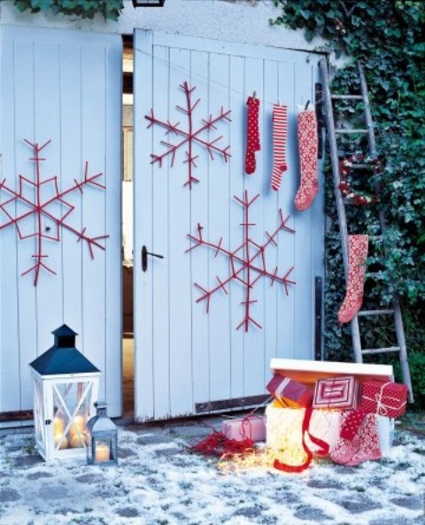 red and white Christmas decor   large snowflakes, stockings and gift boxes plus candle lanterns for a Scandinavian feel