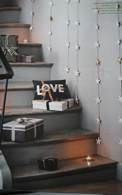 gift boxes and candles right on the steps and star garlands on the wall for a cozy Christmas feel