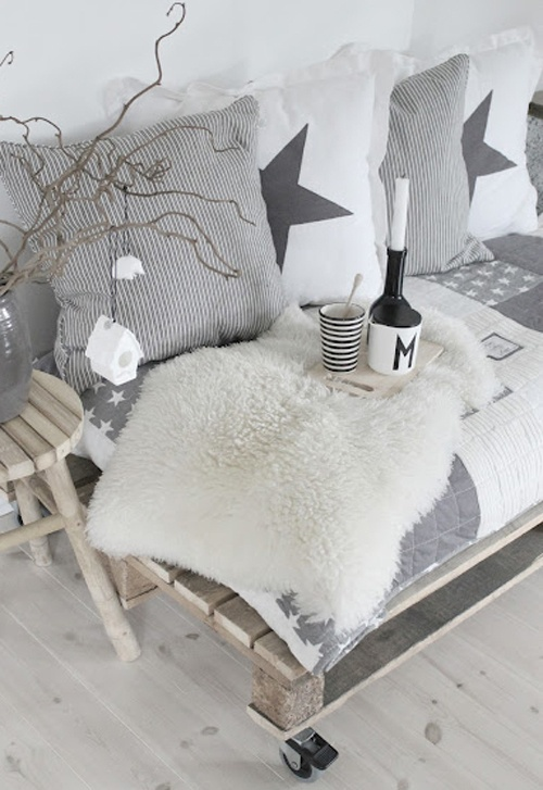a neutral Nordic bench with grey and white Scandi pillows and white faux fur, branches and a toy house ornament for a cozy feel