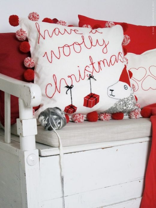 a neutral Christmas bench with white and red pillows with pompoms and a red blanket for Christmas
