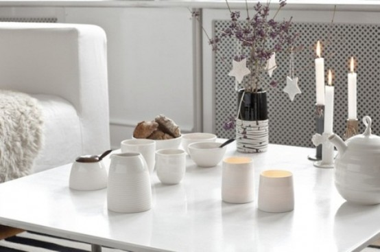 floral branches with white star Christmas ornaments and candles for a cozy Nordic feel at the table