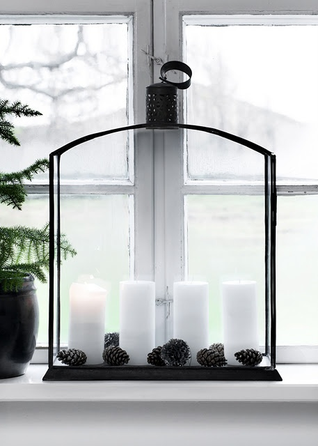 a large black lantern with candles and pinecones is a stylish Nordic decoration