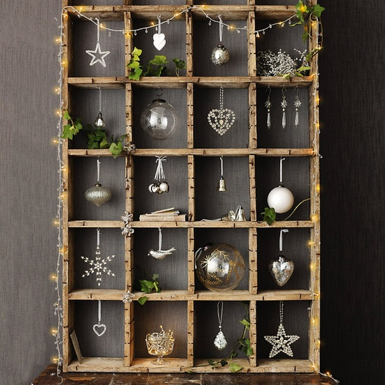 a wooden frame with greenery, lights and an arrangement of Christmas ornaments will be a charming decoration