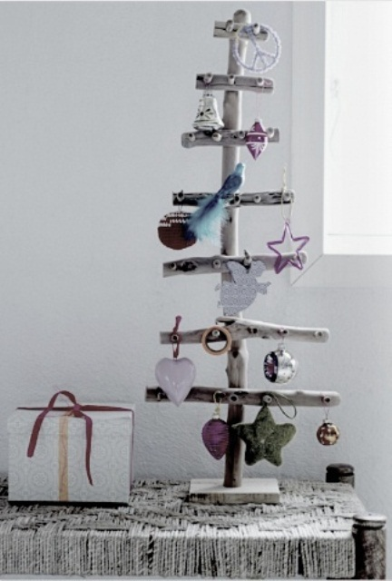 a Christmas tree made of driftwood and with colorful Christmas ornaments is very natural
