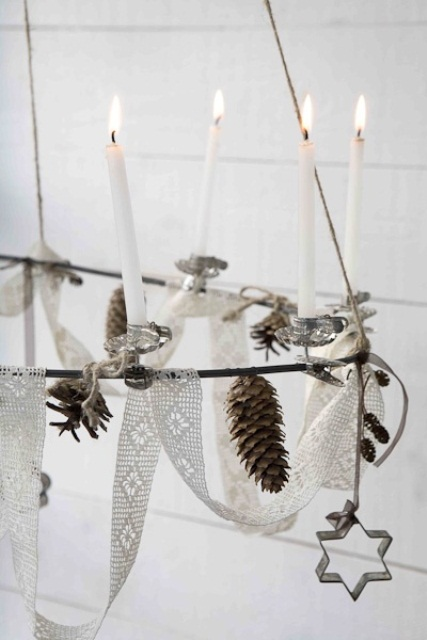 a Nordic chandelier with lace ribbons, pinecones, candles and cookie cutters is a very Nordic and cool idea to go for