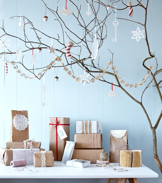 branches with paper and felt ornaments and a garland plus gift boxes wrapped in kraft paper