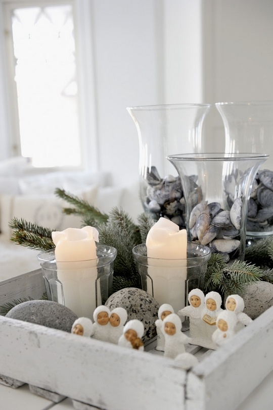 a Nordic Christmas centerpiece of a white tray, mini figurines, evergreens and pebbles plus seashells in glasses