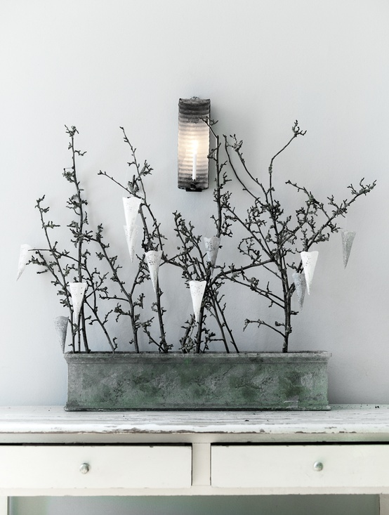 a tin can with branches and white and silver paper cones is a stylish Nordic decoration with a natural feel