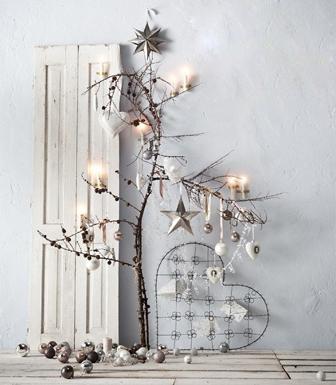 branches with metallic ornaments, pinecones and candles and candles and ornaments under them for a Nordic look