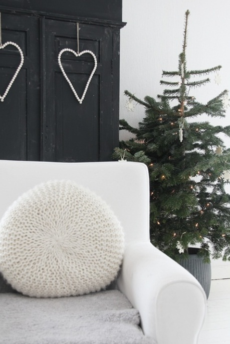 a Christmas tree decorated with lights, white ornaments in a basket looks Scandinavian-like