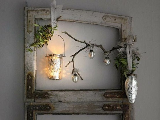 a frame with greenery, branches, metallic ornaments and a candle lantern for a Nordic decoration