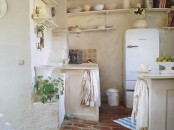 a white stone kitchen with plaster walls, with open shelves, a kitchen island and a modern fridge