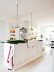 a modern white Scandinavian kitchen with a large kitchen island with a black countertop, pendant lamps and a glass buffet