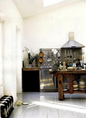 a vintage Scandinavian kitchen with a whitewashed floor and white walls, a rough wood kitchen island, touches of metal and rough wood