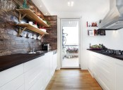 a contemporary meets rustic kitchen with white cabinets and dark countertops and rich stained wood on the wall plus open shelving