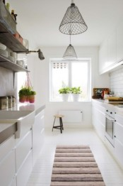 a modern white Scandinavian kitchen with sleek cabinets, mesh pendant lamps and a striped rug