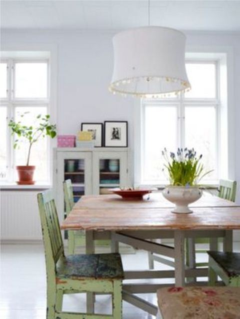 a shabby chic space with a rustic table, green shabby chairs and a pure white backdrop