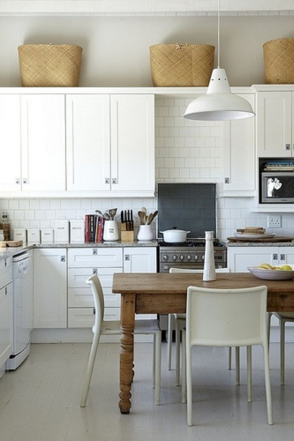 a chic neutral Scandinavian kitchen with vintage cabinets, a white tile backsplash, a rustic wooden table and pendant lamps