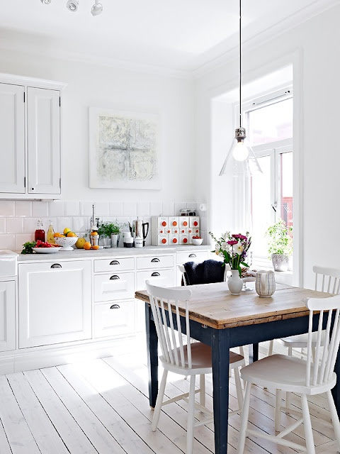 a pure white Scandinavian kitchen with retro cabinets, a glass pendant lamp and a vintage navy dining table
