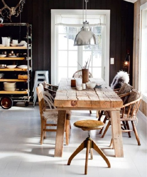 a Nordic kitchen in black and white, a rustic rough wood dining set, a metal pendant lamp and stool
