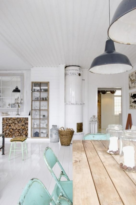 a Nordic kitchen with a wooden table, mint chairs, vintage pendant lamps, a stove and a built-in buffet