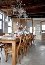 a rustic Scandinavian kitchen with a wooden dining set, whitewashed branches and silver pendant lamps plus a concrete floor