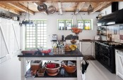a cozy white Scandi kitchen with a large blakc cooker and hood, with a black and white kitchen island and a wooden ceiling with beams and cookware