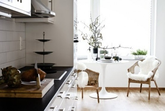 a cozy monochromatic kitchen, a black countertop, wicker chairs, faux fur and a round table