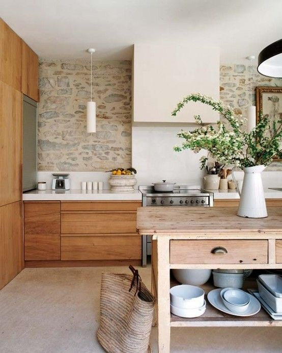 a welcoming earthy tone kitchen with  a stone wall, warm-stained furniture, a wooden kitchen island and pendant lamps