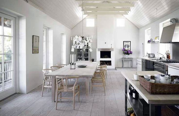 a neutral Nordic kitchen with metal cabinets, a whitewashed dining set and pendant lamps