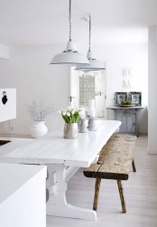 a pure white Scandinavian kitchen with a white rustic table, a rough wooden bench and a light blue cabinet with photos