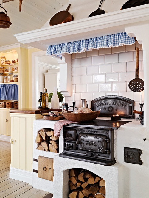 a retro Nordic kitchen with a stove, firewood, white subway tiles, buttermilk cabinets and touches of blue