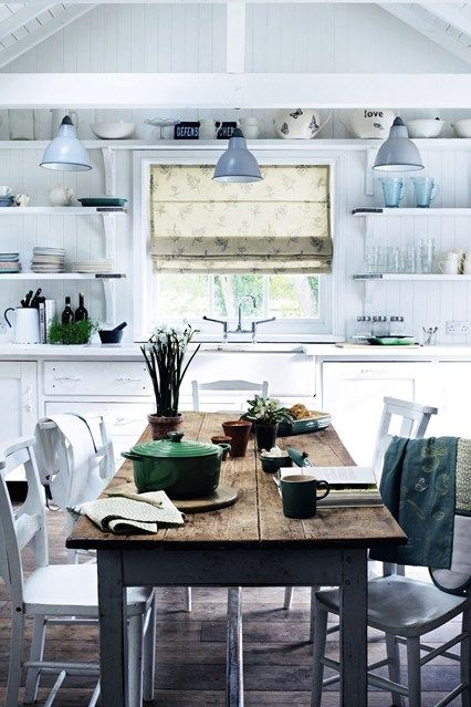 a white Nordic kitchen with shiplap walls, open shelving, vintage cabinets, a rustic table and whitewashed chairs
