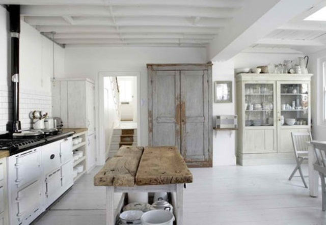 a vintage and shabby chic Scandinavian kitchen with white cabinets, a retro stove, a shabby chic light blue buffet, a glass buffet, a kitchen island with a rough wood top
