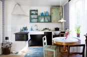 a modern meets vintage Scandi kitchen with black cabinets, a round table, mismatching chairs and shabby chic cabinets in bright colors