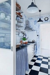 a retro kitchen with a checked floor, blue and white floral wallpaper, open shelves and pendant lamps