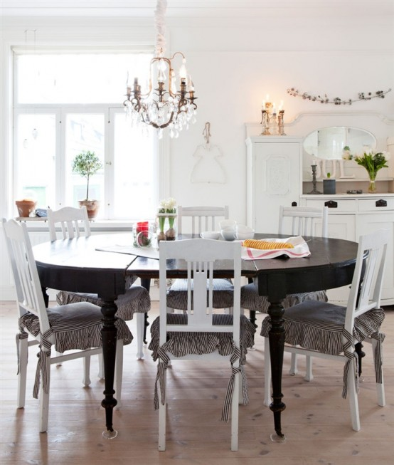 a vintage Scandinavian kitchen with white cabinets, a crystal chandelier, a black round table and white vintage chairs