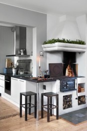 a contemporary meets vintage Scandinavian kitchen with a stove, white cabinets with a black countertop, touches of metal and black stools