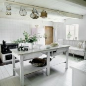 a white Scandinavian kitchen with a vintage touch, a whitewashed kitchen island and bench, white cabinets and a vintage stove