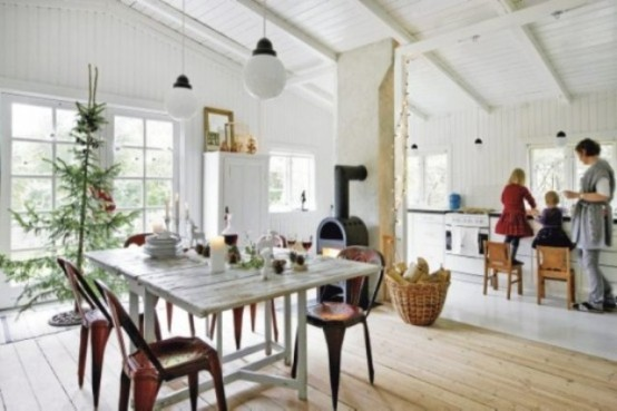a white Scandinavian kitchen with a whitewashed table, white cabinets, a fireplace and pendant lamps