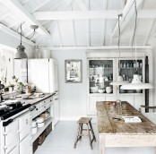 a white Nordic kitchen with a whitewashed buffet, pendant lamps, a rough wooden dining set