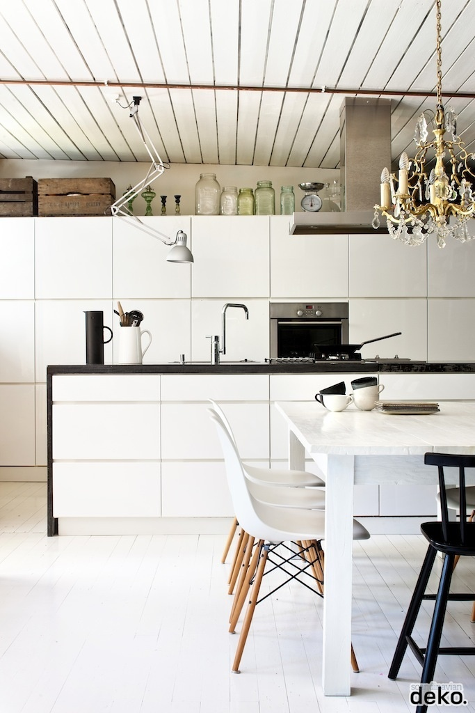 a Nordic off white kitchen with a wooden ceiling, white sleek cabinets and a black countertop, a vintage chandelier and white chairs on wooden legs
