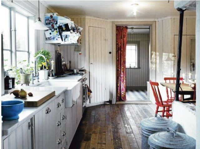 a rustic Scandinavian kitchen with white shiplap cabinets and whitewashed walls, red chairs and touches of blue here and there