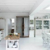 a white Nordic kitchen with an off-white buffet, a white dining set, a shabby chic cupboard and a rustic kitchen island