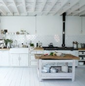 a white Nordic kitchen with white cabinets, a whitewashed kitchen island, a vintage stove and all white surfaces