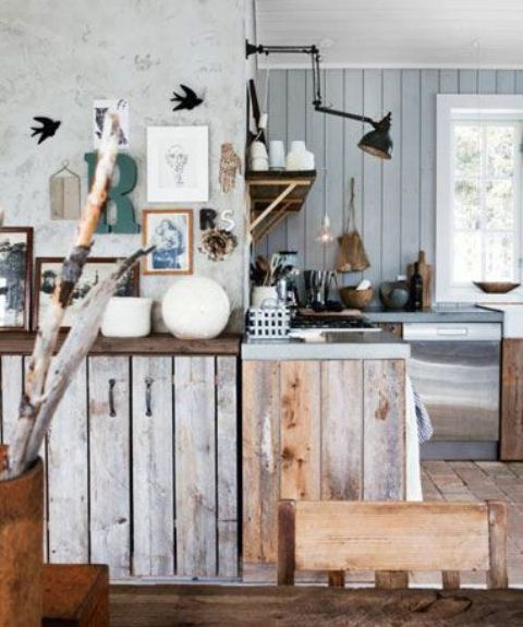 a cozy rustic kitchen with light blue shiplap on the walls, rough wood cabinets, branches and wall lamps