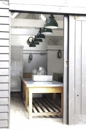 a neutral Scandinavian kitchen done with white tiles, a wood and metal kitchen island and dark pendant lamps